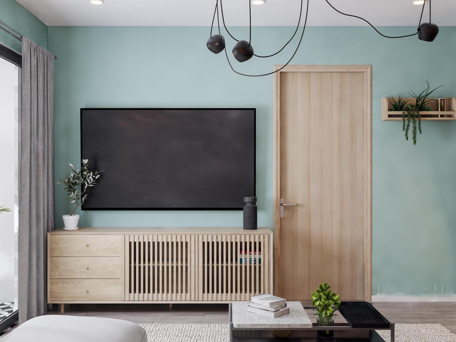 Góc phòng khách căn hộ 90m2 với tường màu xanh pastel nhã nhặn, làm nền cho nội thất gỗ màu sáng trở nên nổi bật hơn.