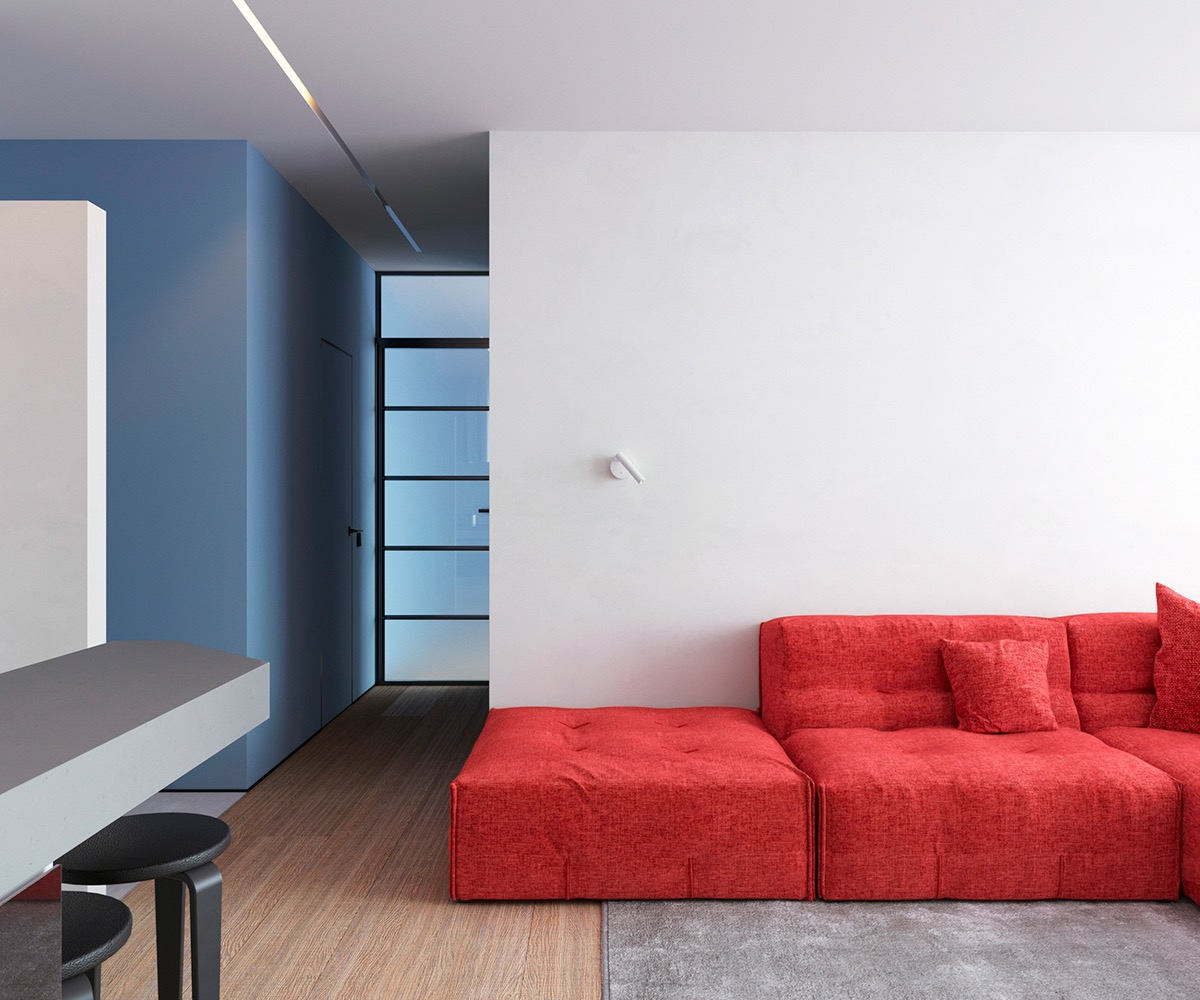 Trong phòng khách căn hộ 64m2, ghế sofa màu đỏ chiếm ưu thế trong khu vực chung, mọi thứ khác được loại bỏ ngoại trừ chiếc đèn treo tường hiện đại màu trắng.