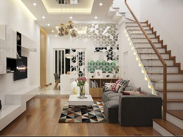 Phòng khách nhà phố tuy không được rộng rãi nhưng bài trí nội thất vô cùng gọn sàng, tiện dụng với sofa xám đậm, bàn trà màu trắng nổi bật trên thảm trải họa tiết hình học màu sắc.