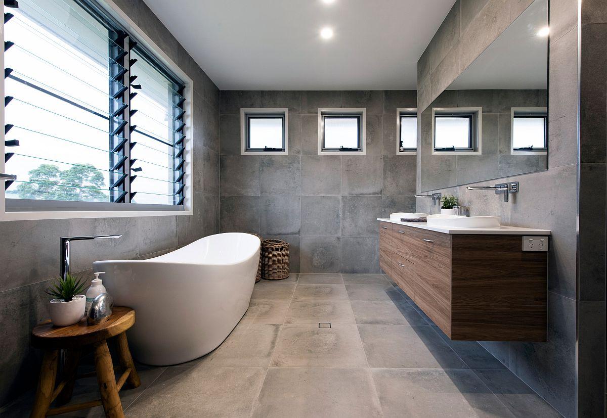 Phòng tắm hiện đại, nổi bật với bồn tắm màu trắng lớn được đặt cạnh khung cửa sổ lớn ngập tràn ánh sáng tự nhiên.