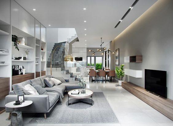 Phòng khách nhà ống sang trọng với bộ ghế sofa màu xám thanh lịch, cùng tông với thảm trải sàn và tường tivi. Lan can cầu thang bằng kính cường lực tạo độ thoáng cho không gian.